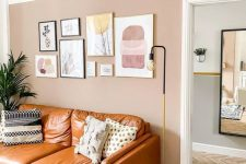 a pretty living room with a blush accent wall, an amber leather sofa, a lovely gallery wall, a woven pendant lamp and potted greenery