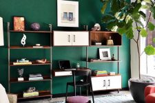 a pretty living room with an emerald accent wall, neutral sofa, jewel tone seating furniture, an open shelving unit and a potted tree