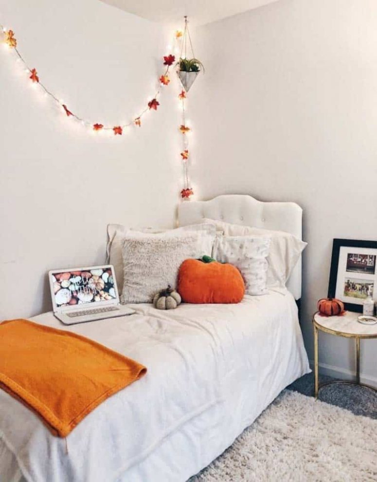 a pretty neutral bedroom styled for the fall with a leaf garland, orange blanket and pumpkin pillows is amazing