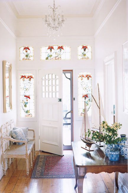 a pretty neutral entryway wiht sidelights with stained glass, a stained table, a vintage bench with blue printed pillows and a crystal chandelier