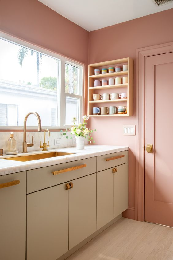 a pretty pastel kitchen with pink walls and a door, olive green cabinets, brass handles and fixtures and a brass built-in sink is super sweet