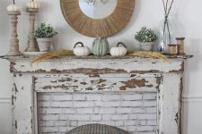 a pretty rustic fall shabby chic mantel with neutral pumpkins, pampas gras,s branches, potted greenery and a mirror in a wooden frame