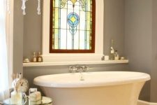a refined bathroom with grey walls, a raised oval tub, a chic stained glass window in Gothic style and a crystal chandelier is wow