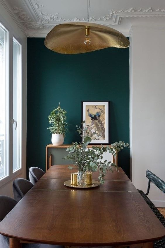 a refined bedroom with a dark green accent wall, a rich stained dining table, a bench, grey chairs, a chic sideboard and a gold pendant lamp