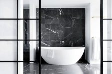 a refined contemporary bathroom done with black marble and black frame French sliding doors separating this bathroom from the rest of the apartment