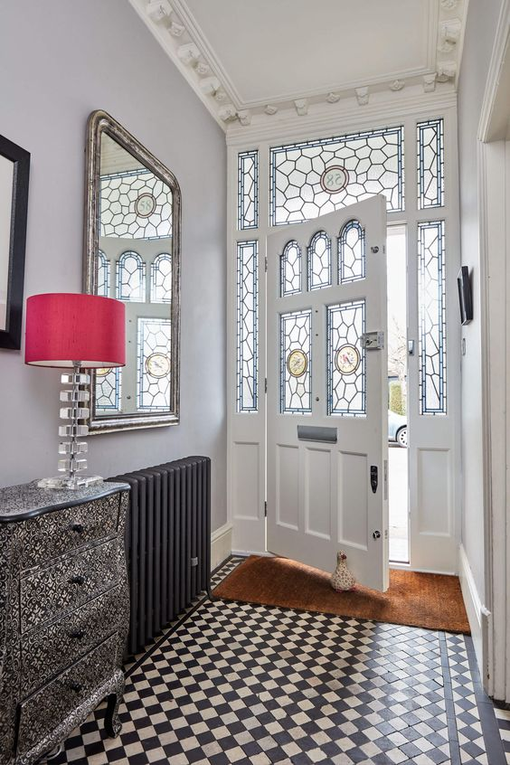 a refined entyway with stained glass sidelights and the door, a checked floor, a printed dress and a red lamp, a mirror and a black radiator