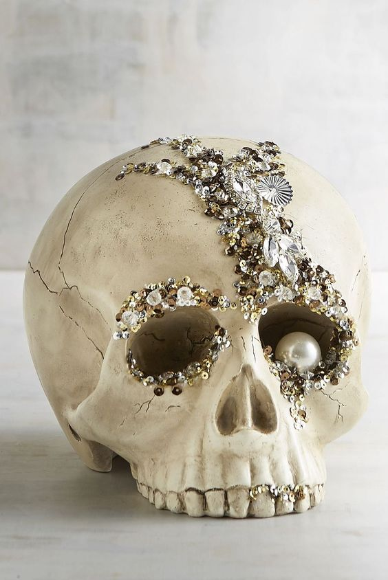 a refined glam Halloween decoration - an embellished skull with rhinestones, sequins and a large pearl as an eye is amazing