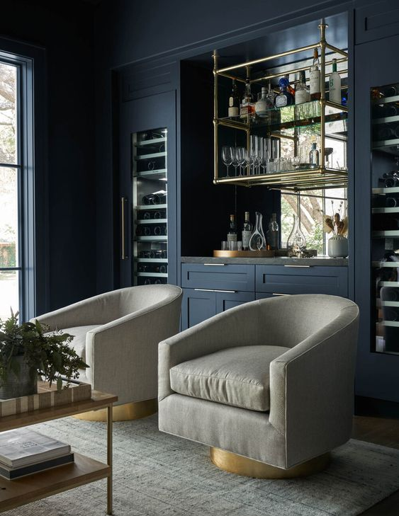 a refined living room with navy walls and a home bar, neutral chairs on brass legs, a brass glass suspended shelf is amazing