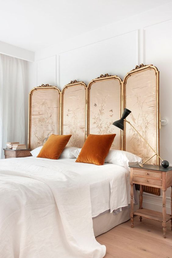 a refined neutral bedroom with a bed, vintage stained nightstands, a vintage screne in brass frames, a brass and black table lamp