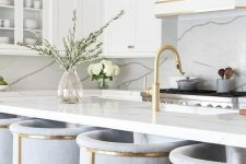 a refined neutral kitchen with white cabinets, a white marble backsplash and countertops, brass fixtures and tall stools with brass framing