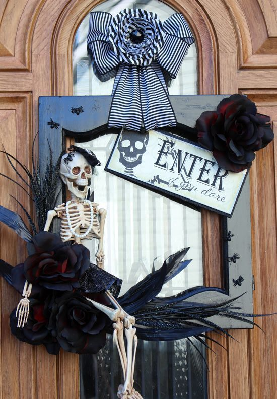 a refined vintage Halloween wreath of a black frame with spiders, a skeleton, dark fauc blooms and a striped bow on top