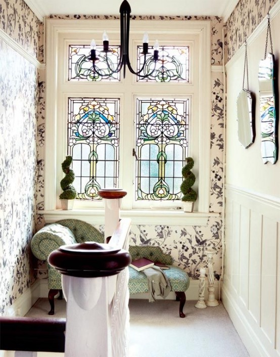 a refined vintage space done with floral wallpaper and a stained glass window plus a chic couch is a fantastic idea