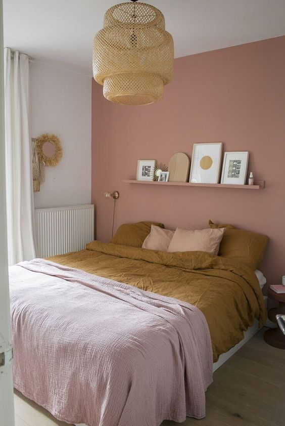 a relaxed and welcoming bedroom with a dusty pink accent wall, a bed, a long open shelf, a nightstand, a woven pendant lamp, some art and mustard and pink bedding