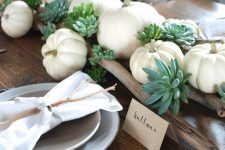 a relaxed rustic Thanksgiving table setting with branches, succulents, white pumpkins, neutral napkins and twigs on each place setting