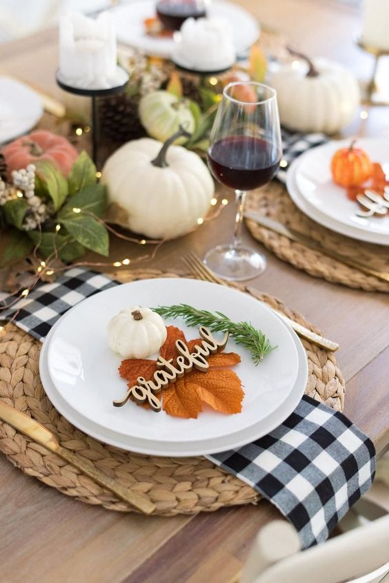 a relaxed rustic Thanksgiving table setting with wovne placemats, plaid napkins, white plates, leaves, greenery, pumpkins and lights