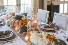 a relaxed rustic Thanksgiving tablescape with a striped runner and woven placemats, printed plates, heirloom pumpkins, candles and blooms