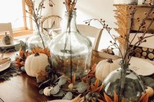 a relaxed rustic Thanksgiving tablescape with leaves, white and green pumpkins, corn cobs and dried blooms is amazing