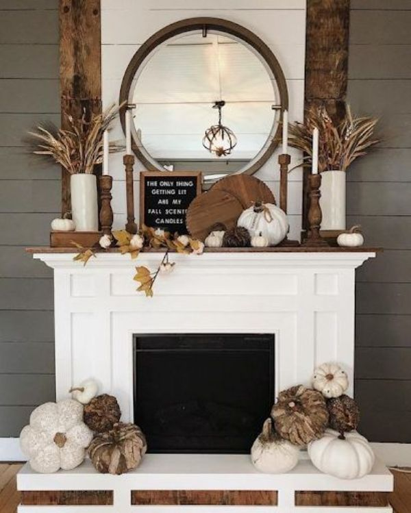 a relaxed rustic fall fireplace with wooden cutting boards, leaves, vine and faux pumpkins, wooden candlesticks and a sign