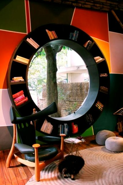 a round window styled as a bookcase, with the view of the garden and lots of books is a unique and bold idea for a reading nook