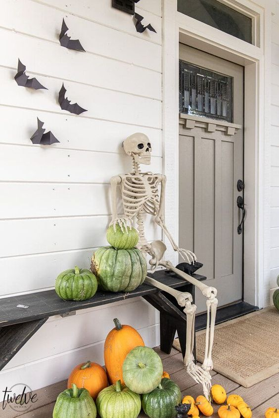a rustic Halloween porch with heirloom pumpkins, a skeleton and some bats on the wall is a cool idea