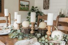 a rustic Thanksgiving table seting with white pumpkins on tree stumps, pillar candles, eucalyptus, silver chargers is chic and stylish