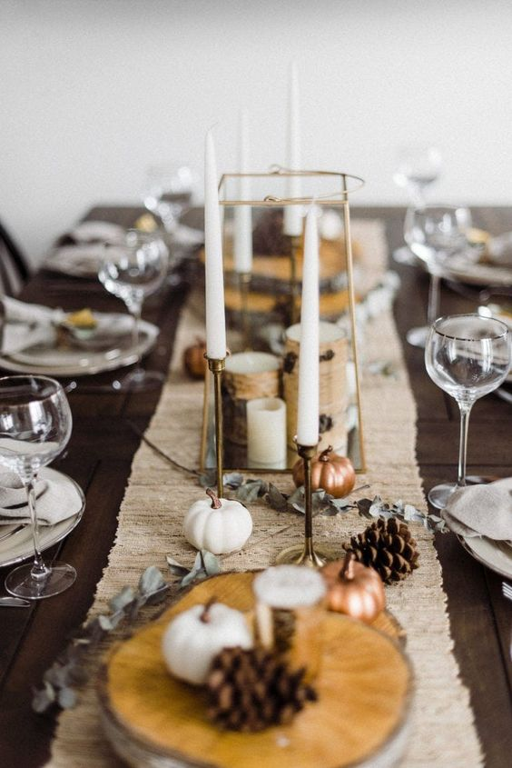 a rustic Thanksgiving tablescape with a linen table runner, pumpkins, pinecones, candles and wood slices is cool