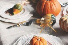a rustic Thanksgiving tablescape with natural pumpkins, vintage plates with gourds and corn cobs and jars
