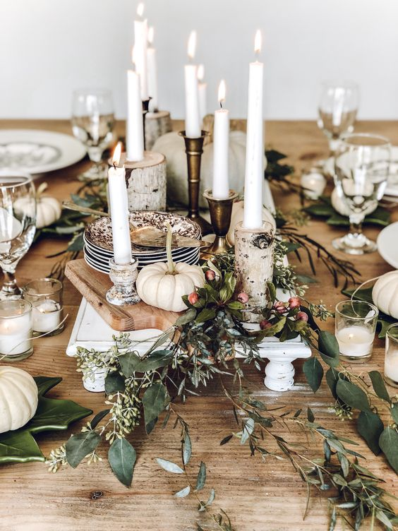 a rustic Thanksgiving tablescape with wooden boards, candles, greenery and berries, white pumpkins and candles is cool