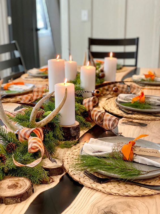 a rustic Thanksgiving tablescape with wovne placemats, antlers, pinecones, evergreens, wood slices and pilalr candles plus plaid