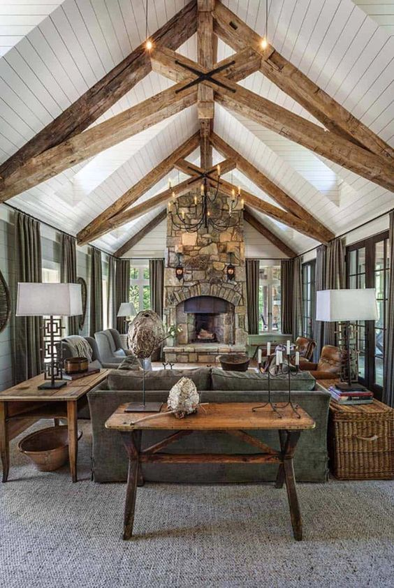 a rustic attic living room with wooden beams, a white planked ceiling, double-height windows, a grey sofa and chairs, a console table and a basket chest