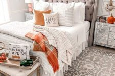 a rustic bedorom with an orange and grey pompom garland, faux pumpkins, pumpkin print bedding and plaid blankets is amazing