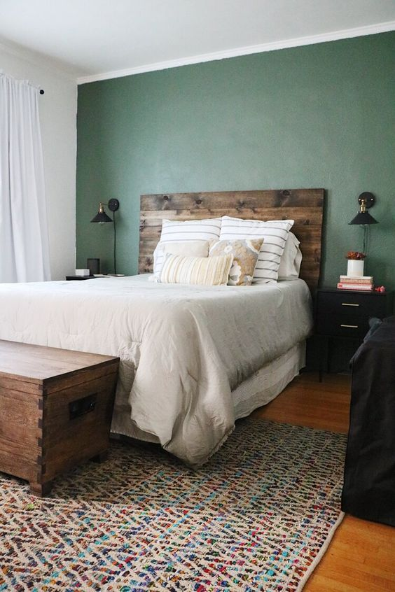a cozy rustic bedroom with a green wall