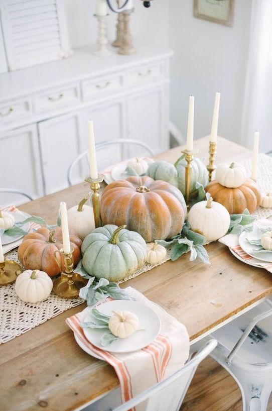 a rustic boho Thanksgiving tablescape with a macrame runner, heirloom pumpkins, candles and striped napkins