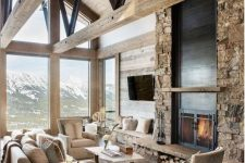 a rustic cabin living room with wooden beams, a fireplace clad with stone, tan seating furniture, a coffee table and a side one that matches