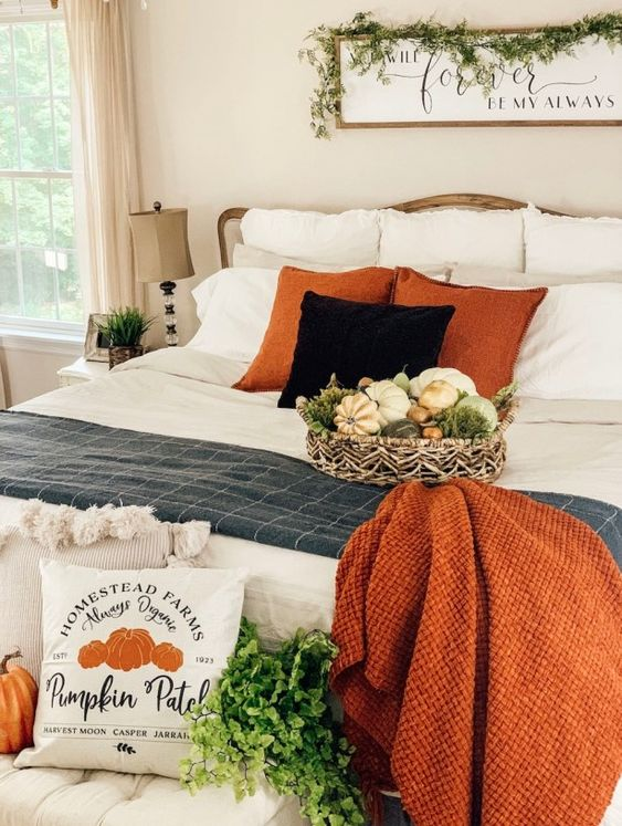 a rustic fall bedroom with a neutral bed and nightstands, a greenery garland and arrangement, orange pillows and a blanket plus a pumpkin print pillow