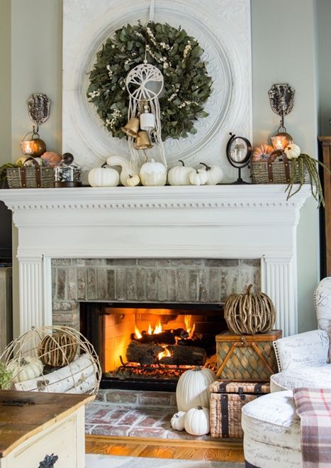 a rustic fall mantel with a greenery wreath, white pumpkins and gourds, baskets with pumpkins and greenery and some candles