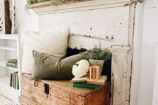 a rustic fall mantel with a vintage feel – with moss, grasses, potted greenery, concrete planters and white pumpkins, a white and green pillow and potted plants