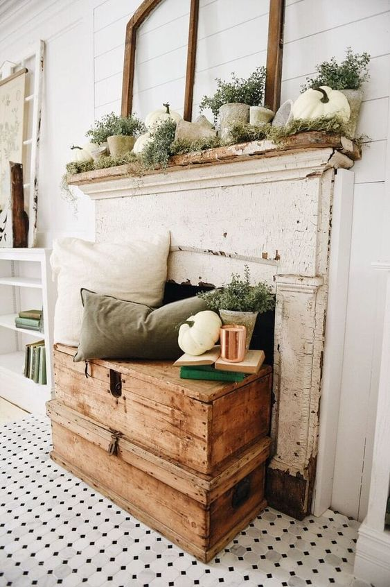 a rustic fall mantel with a vintage feel   with moss, grasses, potted greenery, concrete planters and white pumpkins, a white and green pillow and potted plants