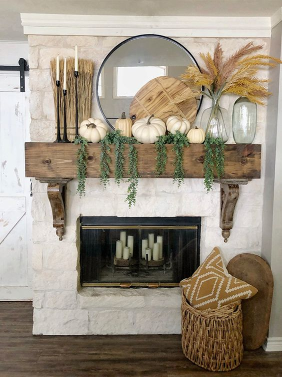 a rustic fall mantel with cascading greenery, white pumpkins, a wooden cutting board, pampas grass, black candlesticks with candles