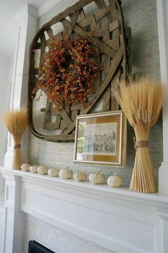 a rustic fall mantel with pumpkins, wheat, a faux berry and leaf wreath and a giant woven basket is a bold idea to style your mantel