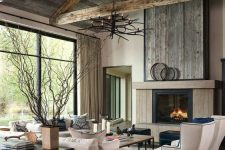 a rustic living room with weathered wooden beams and a ceiling, a fireplace clad with the same wood, neutral seating furniture, black poufs and a console table
