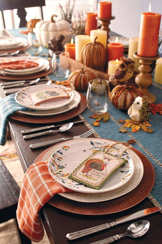 a rustic vintage Thanksgiving tablescape with a blue table runner and blue and orange plaid napkins, faux pumpkins, pillar candles and floral plates