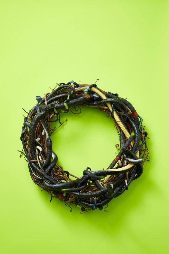 a scary Halloween wreath of vine interwoven with black and green faux snakes is a spooky and a veyr realistic decoration