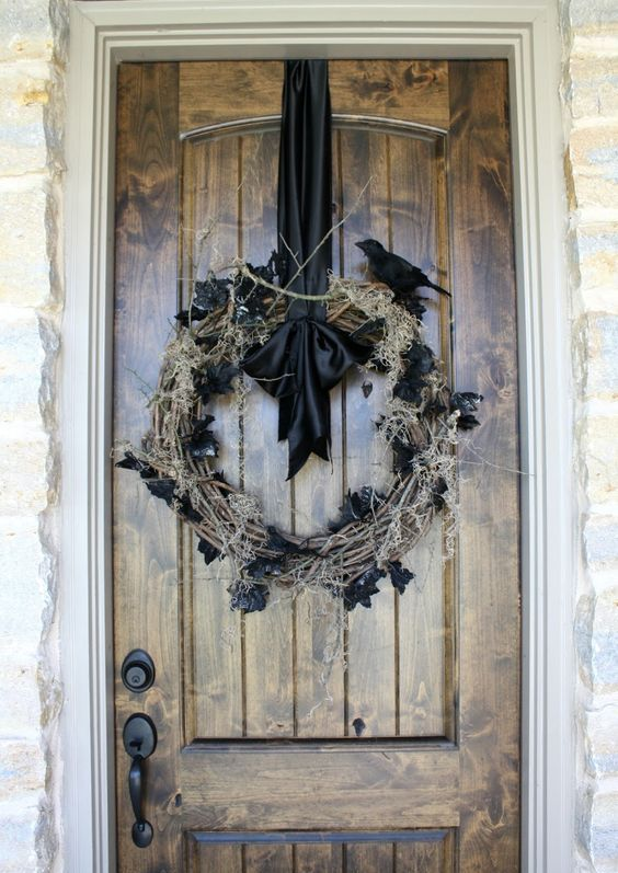 a scary Halloween wreath of vine with moss and black leaves, a faux black bird and a black ribbon is a chic idea you can try