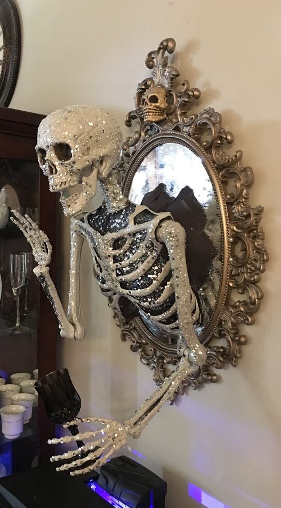 a scary glam Halloween decoration of a vintage mirror with a glam embellished half skeleton attached is elegant