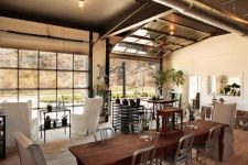 a sectional glass garage door used in an eclectic living room to connect it to the adjacent outdoor spaces