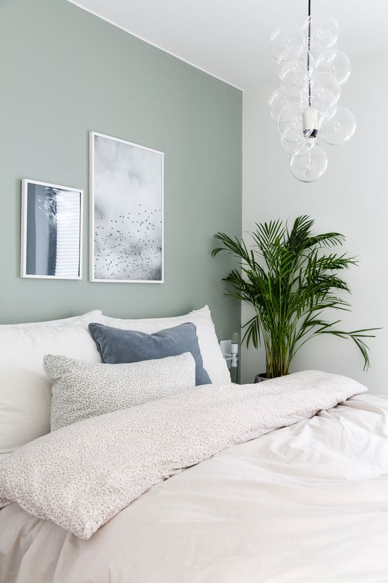 a serene and peaceful bedroom with a pale green accent wall, a bed with neutral bedding, a mini gallery wall, a bubble chandelier and neutral bedding