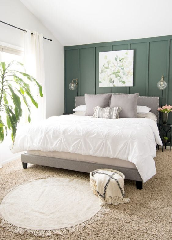 a serene bedroom with a green paneled wall, a grey upholstered bed with neutral bedding, layered rugs and a potted plant plus an artwork