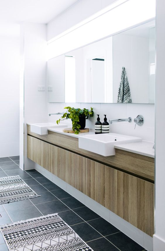 a serene contemporary bathroom with a black tile floor, a light-stained built-in vanity and a large mirror, a clerestory window