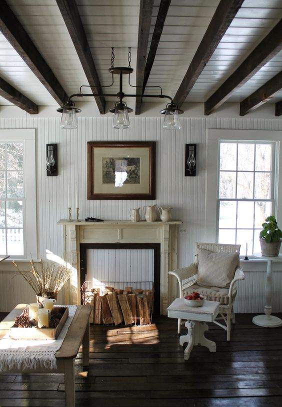 a shabby chic living room with white planked walls and a ceiling, dark-stained wooden beams, neutral vintage furniture and a faux fireplace